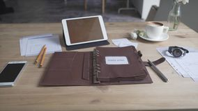 Beautiful close up view on business work area desktop with tablet cell phone coffee mug watch leather note pad. Close up shot of elegant light brown leather case stock video footage