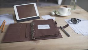 Beautiful close up view on business work area desktop with tablet cell phone coffee mug watch leather daily planner book. Beautiful close up shot on business stock video