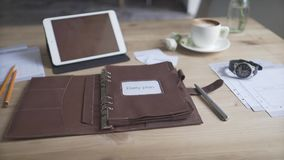 Beautiful close up view on business work area desktop with tablet cell phone coffee mug watch leather planner journal. Beautiful close up shot on business work stock video footage