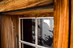 Beautiful close-up view of an old, weathered wooden window with a big window frame seen at a mountain cabin in the Swiss Alps, Swi Stock Images
