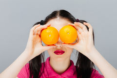 Beautiful close-up young woman with oranges. Healthy food concept. Skin care and beauty. Vitamins and minerals. gray royalty free stock image