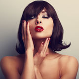 Beautiful closed eyes woman touching face. Red lipstick and nail Stock Photography