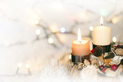 Closeup of Advent wreath with two burning candle and Christmas lights in background. Beautiful closeup of Advent wreath with two burning candle and white royalty free stock photography