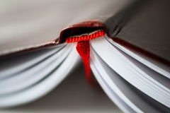 A beautiful closeup of a book in dark red cover and with red bookmark. Royalty Free Stock Photos