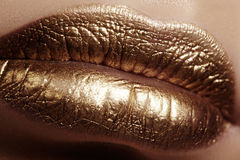 Beautiful closeup with female plump lips with gold color makeup. Fashion celebrate make-up, glitter cosmetic Stock Images