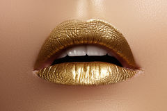 Beautiful closeup with female plump lips with gold color makeup. Fashion celebrate make-up, glitter cosmetic royalty free stock image