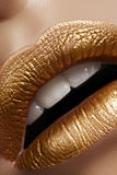 Beautiful closeup with female plump lips with gold color makeup. Fashion celebrate make-up, glitter cosmetic Stock Photography