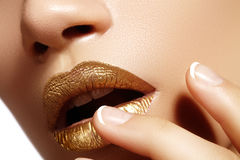 Beautiful closeup with female plump lips with gold color makeup. Fashion celebrate make-up, glitter cosmetic Royalty Free Stock Photos