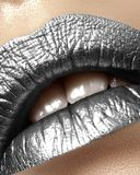 Beautiful closeup with female plump lips with silver color makeup. Christmas celebrate make-up, glitter sparkles on lip. Shine christmas style. Metalic makeup royalty free stock photography