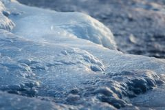 A beautiful closeup of a frozen sea water on the coast of Baltic sea. Frozen salt water vawes on a beach. Abstract closup of ice Royalty Free Stock Photo
