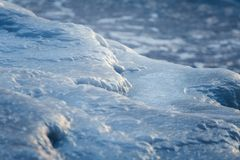 A beautiful closeup of a frozen sea water on the coast of Baltic sea. Frozen salt water vawes on a beach. Abstract closup of ice Royalty Free Stock Photos
