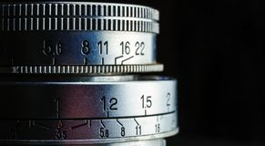 Beautiful closeup of an old vintage camera lens with aperture values  on a black background. Photography concept with copy Royalty Free Stock Photos