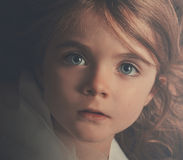 Beautiful Closeup of Serious Little Girl. A young little child is looking into the camera with a serious expression. The closeup of the girl shows her hair and stock photo
