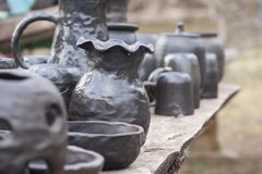 Unique handmade black pottery from clay just taken out from kiln. Beautiful closeup of unique handmade black pottery from clay on wooden table just taken out stock photography