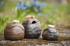 Beautiful closeup of unique handmade three pots on green moss in summer with blue flowers in background. Beautiful closeup of unique handmade three pots on green Stock Photography