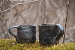 Unique handmade two cups with folk signs on green moss with blurred forest on background. Beautiful closeup of unique handmade two cups with folk signs on green Royalty Free Stock Photos