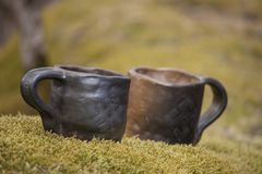 Closeup of unique handmade two cups with folk signs on green moss with blurred forest on background. Beautiful closeup of unique handmade two cups with folk Royalty Free Stock Photography