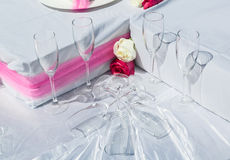 Beautiful closeup view of wedding decorated part of table with glasses and roses Royalty Free Stock Image