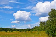 Beautiful clouds and blue sky against green meadows. Picturesque summer landscape royalty free stock images