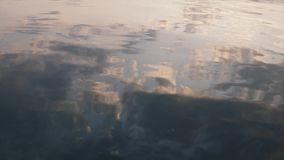 Beautiful clouds illuminated by sunrise beams reflecting in calm sea water surface closeup nature background. Slow motion stock footage
