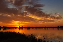 Beautiful clouds over the cane during sunset in lake Zoetermeerse plas Stock Images
