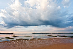 Beautiful clouds over shallow waters and sandy beach. Minimalist. Ic Australian landscape stock photo