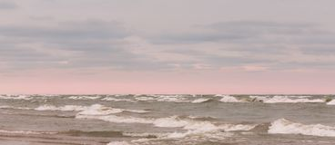 Beautiful clouds and pink glowing sky over choppy waves stock photography