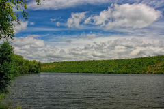 Beautiful clouds in the sky over the lake. Green trees Royalty Free Stock Photo