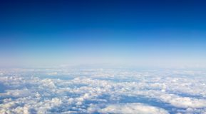 The beautiful cloudscape with clear blue sky. A view from airplane window royalty free stock image