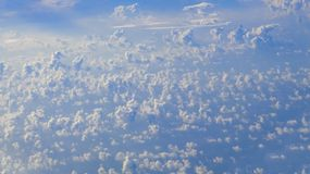 The beautiful cloudscape with clear blue sky. A view from airplane window royalty free stock photography