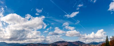 Beautiful cloudscape over the mountain ridge. Lovely nature background with blue sky and fluffy clouds on autumn day Royalty Free Stock Photo