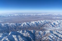 Beautiful cloudscape and snow mountains from plane window stock photo