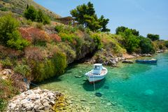 Boat on crystal clear water of ionian sea in Porto Palermo in Albania stock image