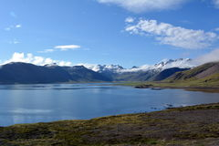 Beautiful coast of the fjord at the forefront of the snowy peaks in the west of Iceland.  royalty free stock photography