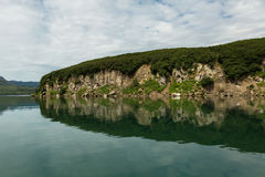 Beautiful coast of Kurile Lake is reflected in the water. Royalty Free Stock Photography