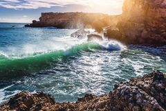 Beautiful coast of the ocean, Algarve, Portugal. Waves break aga. Inst the rocks in the sun royalty free stock image