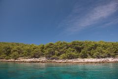 Beautiful coastline with green forest, stones and blue sky and sea water. Natural wallpaper. Adriatic coastline. Croatia. Mediterranean sea stock photography