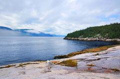 Beautiful coastline. With gulls and misty high mountains, Tadoussac, Quebec, Canada Stock Photo