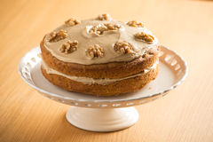 Beautiful Coffee and Walnut Cake. Beautifully presented Coffee and Walnut cake on a white cake stand Stock Image