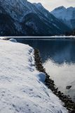 Beautiful cold pure winter scenery on lake lago del predil in sunlight and blue sky, julina alps, Italy Stock Image