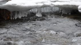 Beautiful cold running fresh river water and ice macro video. In wintertime stock footage