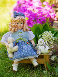 Beautiful collectible doll in the garden bloom. Garden still life with collectable doll Stock Image