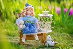 Beautiful collectible doll in the garden bloom Royalty Free Stock Photography
