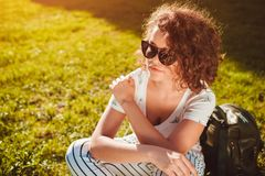Beautiful college girl chilling sitting on lawn in campus park. Stylish woman wearing glasses outdoors royalty free stock image