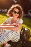 Beautiful college girl chilling sitting on lawn in campus park. Stylish woman wearing glasses outdoors stock photography