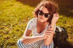 Beautiful college girl chilling sitting on lawn in campus park. Stylish woman wearing glasses outdoors stock photo