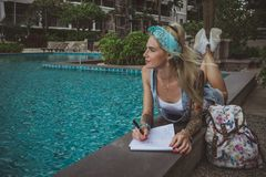 A beautiful college student at the pool performs homework. Dreamy image of a modern girl. Model of tattoo. royalty free stock image