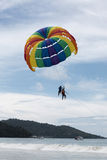 Beautiful color large parachute in the blue sky tropical beach. Two Chinese tourists flying on a parachute over the sea on a beach Royalty Free Stock Photo