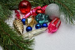 New Year`s bright colored toys and pine branches on a gray background. Beautiful colored New Year`s toys in green coniferous branches stock image