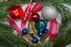 New Year`s bright colored toys and pine branches on a gray background. Beautiful colored New Year`s toys in green coniferous branches stock photo